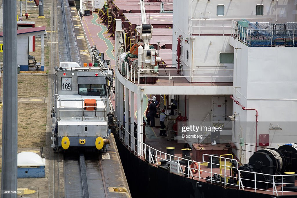 An electric locomotive, known a a mule, guides the CMB Coralie dry bulk carrier through the Miraflores Locks at the Panama Canal near Panama City, Panama, on Wednesday, April, 23, 2014. Construction projects throughout Panama have remained idle since April 23, when workers walked off the job in an effort to win a 35 percent salary increase. The strike threatens to further delay the canals expansion, designed to accommodate larger ships and help reduce transport costs for commodities such as liquefied natural gas. Photographer: Susana Gonzalez/Bloomberg via Getty Images