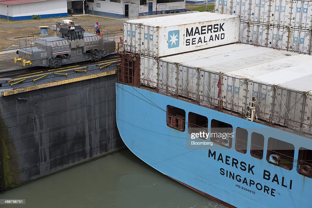 An electric locomotive, known as a mule, top left, guides the Maersk container ship Bali through the Miraflores Locks at the Panama Canal near Panama City, Panama, on Wednesday, April, 23, 2014. Construction projects throughout Panama have remained idle since April 23, when workers walked off the job in an effort to win a 35 percent salary increase. The strike threatens to further delay the canals expansion, designed to accommodate larger ships and help reduce transport costs for commodities such as liquefied natural gas. Photographer: Susana Gonzalez/Bloomberg via Getty Images