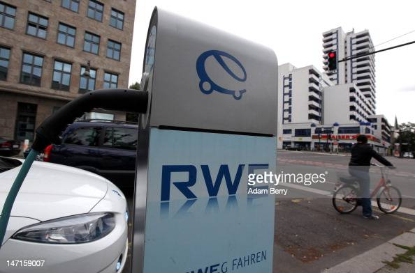 An electric Renault Fluence ZE automobile sits plugged into an RWE electric car charging station on the street as a cyclist passes on June 26 2012 in...