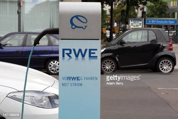 An electric Renault Fluence ZE automobile sits plugged into an RWE electric car charging station on the street near a Smart car on June 26 2012 in...