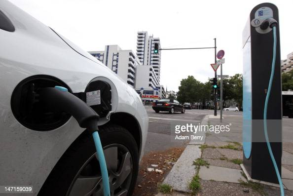 An electric Renault Fluence ZE automobile sits plugged into an RWE electric car charging station on the street on June 26 2012 in Berlin Germany A...