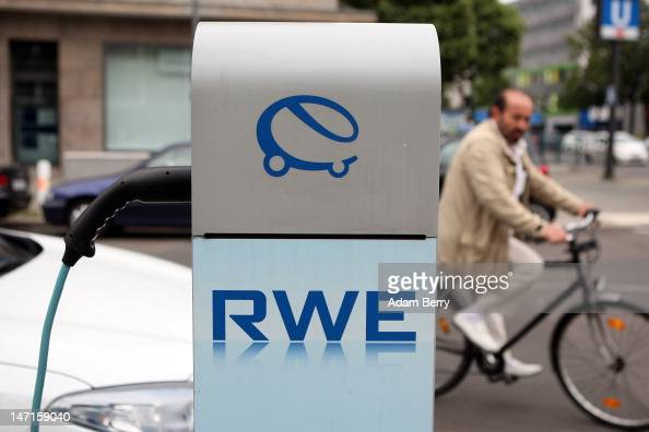 An electric Renault Fluence ZE automobile sits plugged into an RWE car charging station on the street as a man on a bicycle passes on June 26 2012 in...