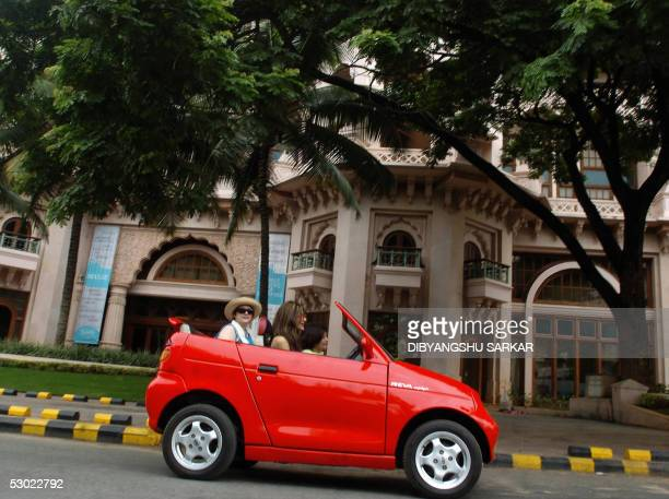 An electric Reva motorcar drives along a busy city street during a rally to celebrate World Environment Day in Bangalore 05 June 2005 The rally was...