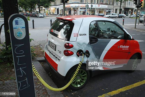 An electric Smart car part of the Flinkster carsharing program of German state railway company Deutsche Bahn stands parked while being charged on...