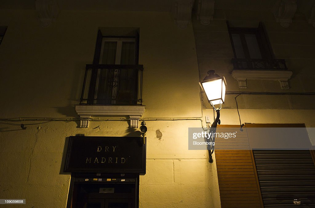An electric street lamp hangs from a building outside the 'Dry Madrid' bar in Madrid, Spain, on Sunday, Jan. 6, 2013. In December, the Spanish parliament passed an energy law that imposed a 7 percent tax on electricity generation from Jan. 1 to plug the deficit. Photographer: Angel Navarrete/Bloomberg via Getty Images Jan. 1 to plug the deficit. Photographer: Angel Navarrete/Bloomberg via Getty Images