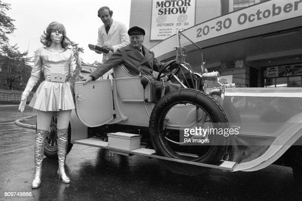 ** An electric 'supergirl' dressed entirely in silver arrives at Earl's Court for the Motor Show Lord Montagu chauffeurs her in a 1906 Silver Ghost...