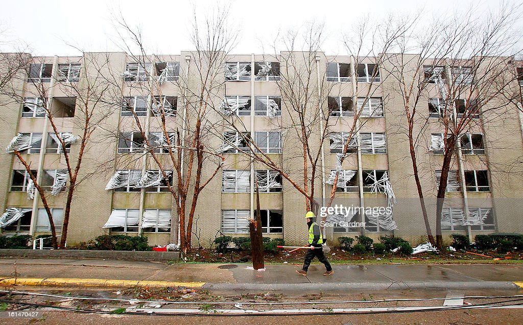 An electrical crewman walks in front of a building with blown out windows on Hardy Street across from the University of Southern Mississippi after a tornado touched down yester evening on February 11, 2013 in Hattiesburg, Mississippi. Hundreds of homes were destroyed and over sixty people injured when the tornado ripped through the town.