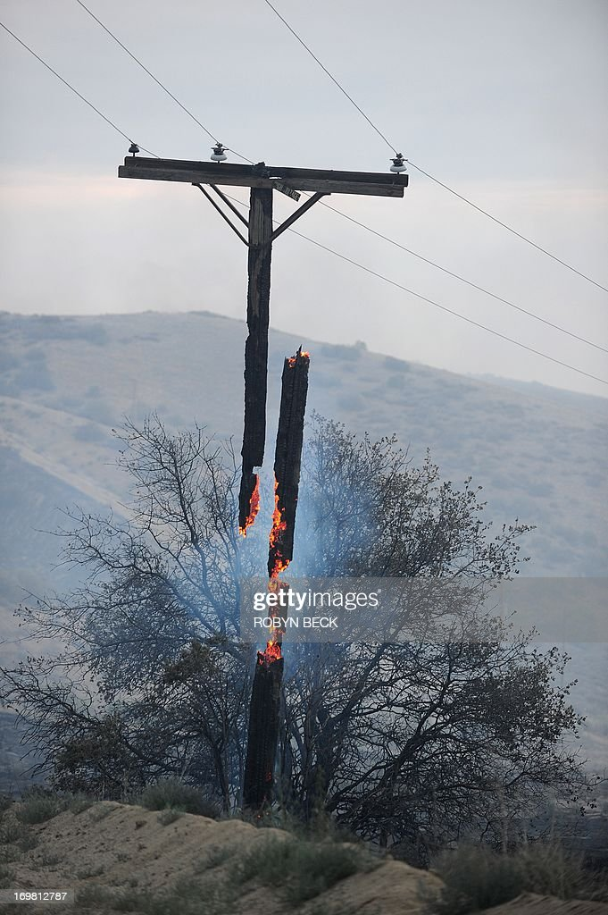 An electrical line pole burns in two pieces after the Powerhouse wildfire ripped through the area overnight, in Lake Hughes, California, approximately 66 miles (100 km) north of Los Angeles in the Angeles National Forest, June 2, 2013. The wind-fueled Powerhouse Fire has ravaged over 19,500 acres, destroyed at least five homes and is threatening over 1,000 more structures. It is 20 percent contained, according to the Los Angeles County Fire Department.