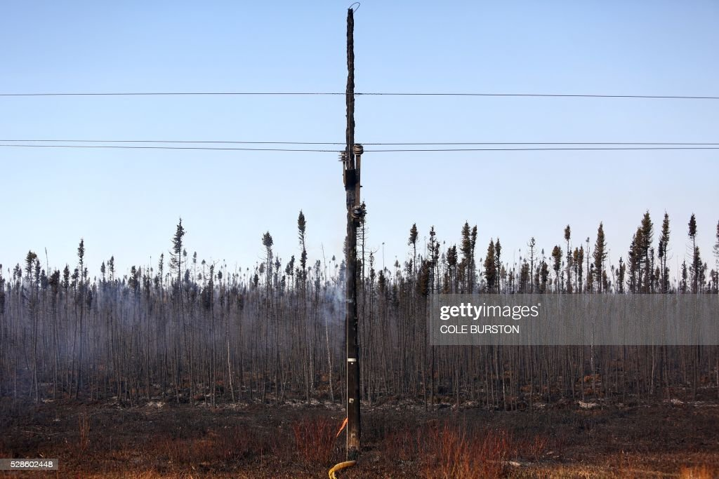 An electrical pole smoulders on the side of the highway near Fort McMurray, Alberta on May 6, 2016. Canadian police led convoys of cars through the burning ghost town of Fort McMurray Friday in a risky operation to get people to safety far to the south.In the latest chapter of the drama triggered by monster fires in Alberta's oil sands region, the convoys of 50 cars at a time are driving through the city at about 50-60 kilometers per hour (30-40 miles per hour) TV footage showed. / AFP / Cole Burston