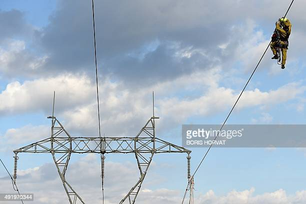 An electrician installs a marker on a hightension line of 225 000 volts on October 9 in Eygalieres southern France To prevent birds of prey colliding...