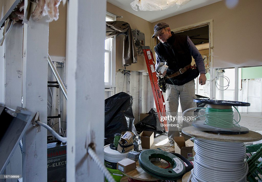 An electrician looks for supplies while doing repairs on a home in the Staten Island borough of New York, U.S., on Wednesday, Nov. 28, 2012. Superstorm Sandy is giving the U.S. Northeast, and the rest of the country, an economic boost that may eventually surpass the loss of business it caused. Photographer: Jin Lee/Bloomberg via Getty Images