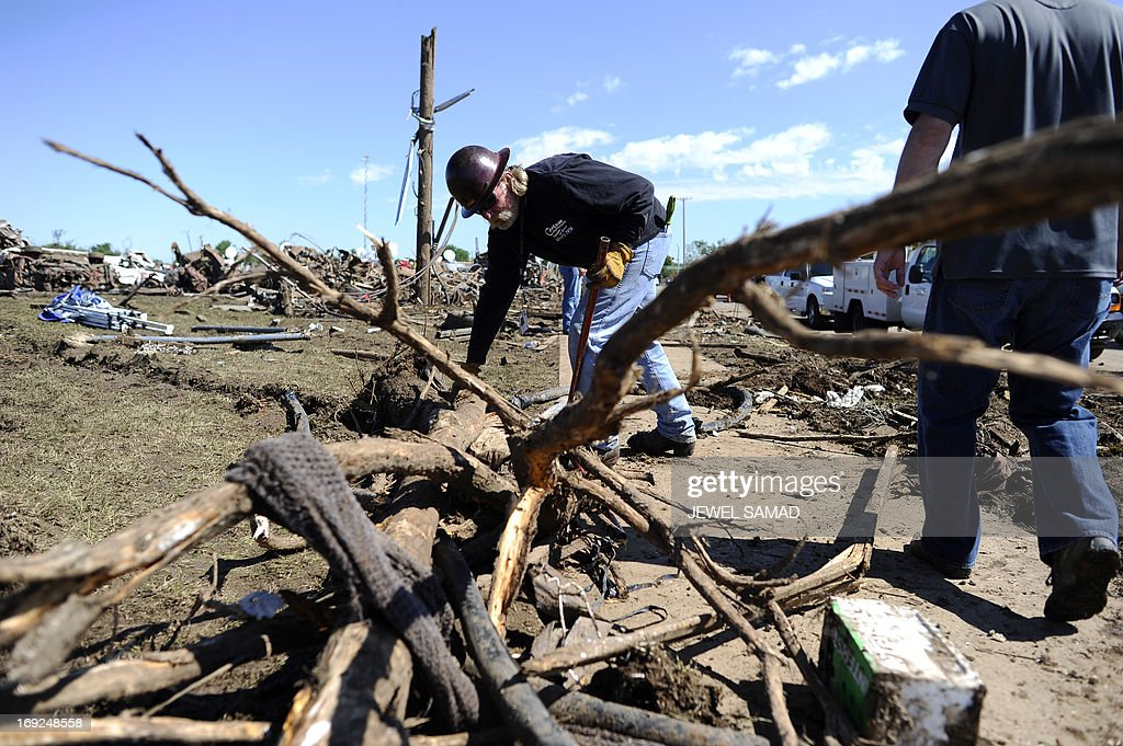 An electricity company employee works to clean up wires at a tornado-devastated neighborhood on May 22, 2013 in Moore, Oklahoma. As rescue efforts in Oklahoma wound down, residents turned to the daunting task of rebuilding a US heartland community shattered by a vast tornado that killed at least 24 people. The epic twister, two miles (three kilometers) across, flattened block after block of homes as it struck mid-afternoon on May 20, hurling cars through the air, downing power lines and setting off localized fires in a 45-minute rampage.AFP PHOTO/Jewel Samad
