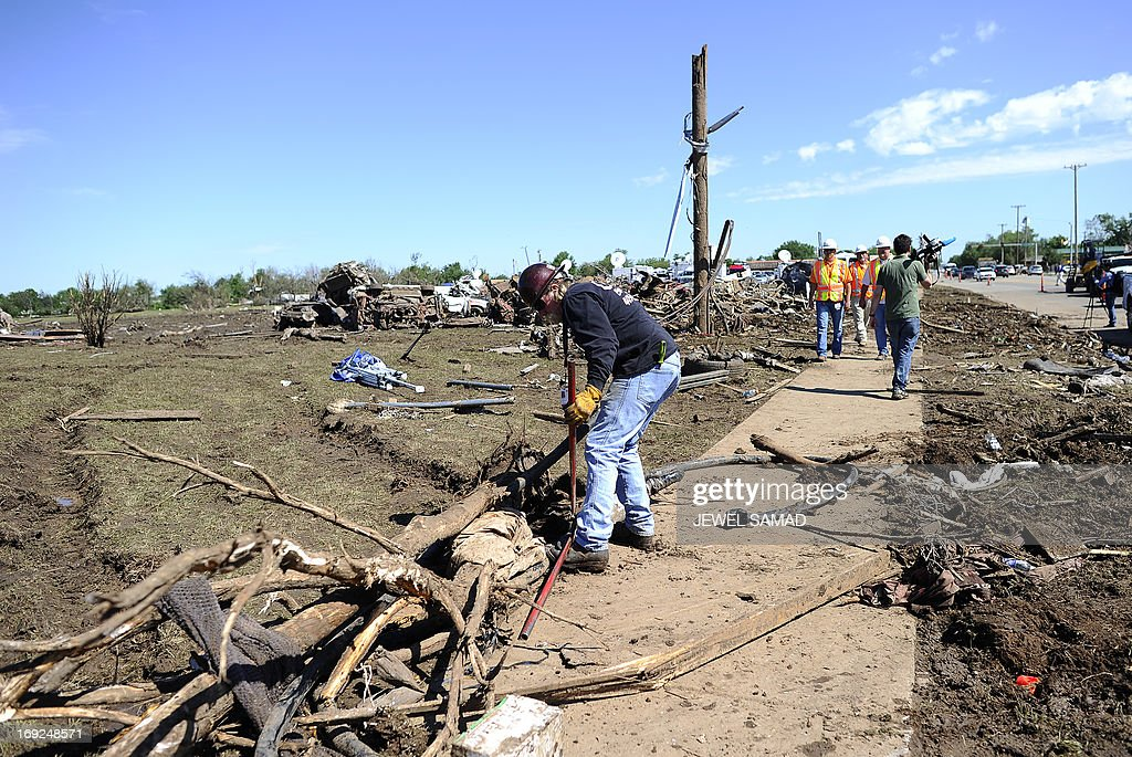 An electricity company employee works to clean up wires at a tornado-devastated neighbourhood on May 22, 2013 in Moore, Oklahoma. As rescue efforts in Oklahoma wound down, residents turned to the daunting task of rebuilding a US heartland community shattered by a vast tornado that killed at least 24 people. The epic twister, two miles (three kilometers) across, flattened block after block of homes as it struck mid-afternoon on May 20, hurling cars through the air, downing power lines and setting off localized fires in a 45-minute rampage.AFP PHOTO/Jewel Samad