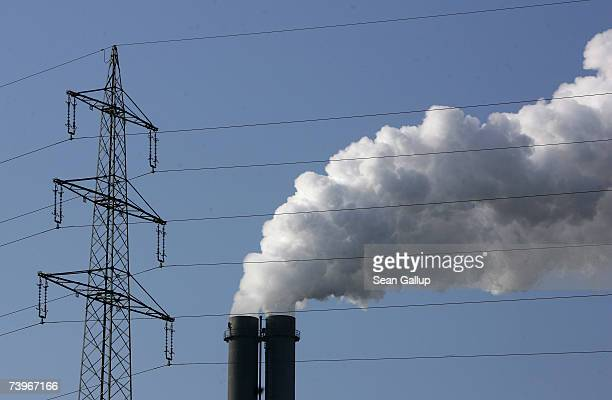 An electricity pylon stands in front of the exhaust pluming from the main chimneys of the black coalfired power plant Heizkraftwerk Reuter West March...
