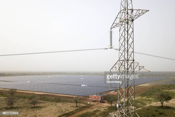 An electricity pylon tower stands as photovoltaic solar panels sit in an array beyond at the Senergy Santhiou Mekhe PV solar plant in Thies Senegal...