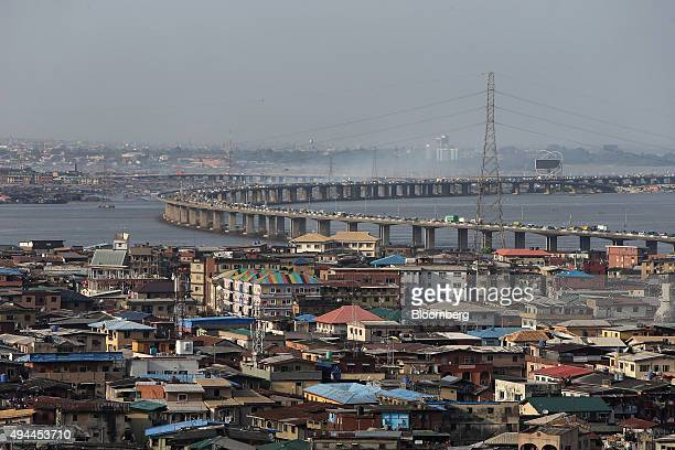 An electricity pylons carries power cables above residential property as traffic passes across a bridge from Isale Eko on Lagos Island towards the...