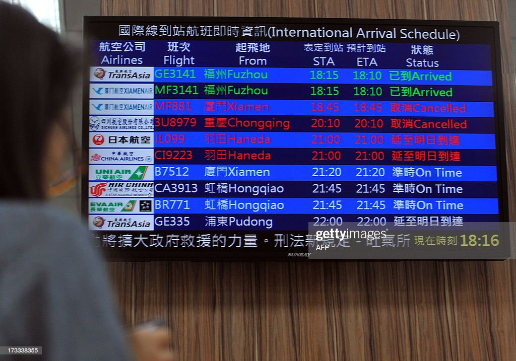 An electronic board showing disruptions to air travel is displayed at Taipei's main station as Typhoon Soulik approaches northern Taiwan on July 12, 2013. Hundreds of villagers were evacuated and schools and businesses shut down in Taiwan on July 12 as it prepared for the arrival of Typhoon Soulik, expected to pound the island with powerful winds and heavy rain over the weekend. AFP PHOTO / Mandy CHENG