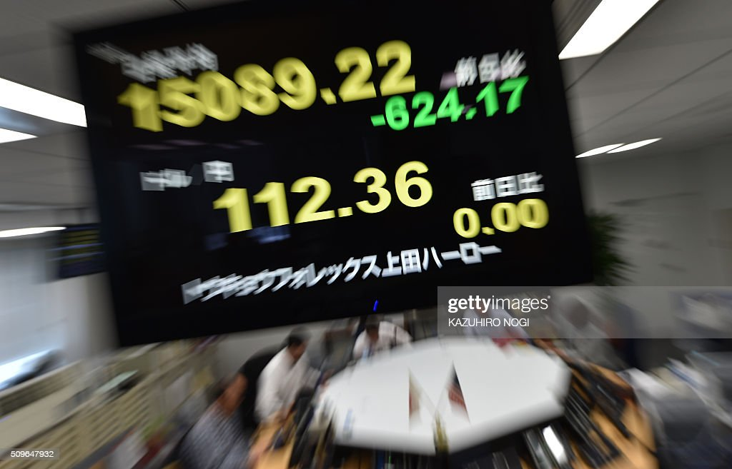 An electronic board shows a share price numbers of the Tokyo Stock Exchange and a foreign exchange rate numbers against US dollar at a foreign...