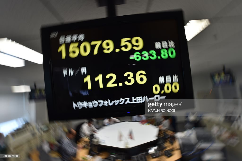 An electronic board shows a share price numbers of the Tokyo Stock Exchange (upper) and a foreign exchange rate numbers against US dollar (bottom) at a foreign exchange brokerage in Tokyo on February 12, 2016. Tokyo stocks tumbled more five percent in early deals on February 12, playing catch-up with a global sell-off after a one-day holiday amid deepening worries about the world economy and as a stronger yen hammered exporters. AFP PHOTO / KAZUHIRO NOGI / AFP / KAZUHIRO NOGI