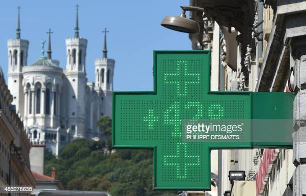 An electronic display of a pharmacy indicates 42 degrees Celsius while the Fourviere basilic is seen in the background during a heat wave in Lyon...