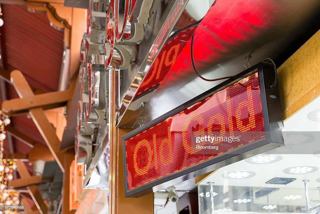 An electronic display sign reading 'Old Gold' hangs outside a gold store in the Dubai Gold Souk in the Deira district of Dubai, United Arab Emirates, on Tuesday, July 2, 2013. Gold swung between gains and losses in London as investors weighed prospects for increased physical demand against a slowing stimulus in the U.S. Photographer: Duncan Chard/Bloomberg via Getty Images