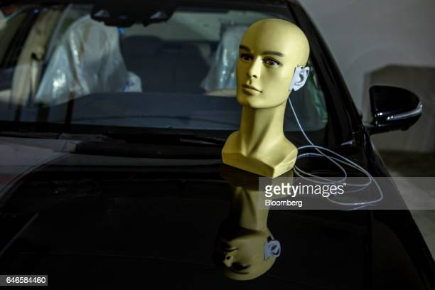 An electronic dummy head for testing sound perception sits on the hood of an automobile during research at the Noveto Systems Ltd office in Petach...