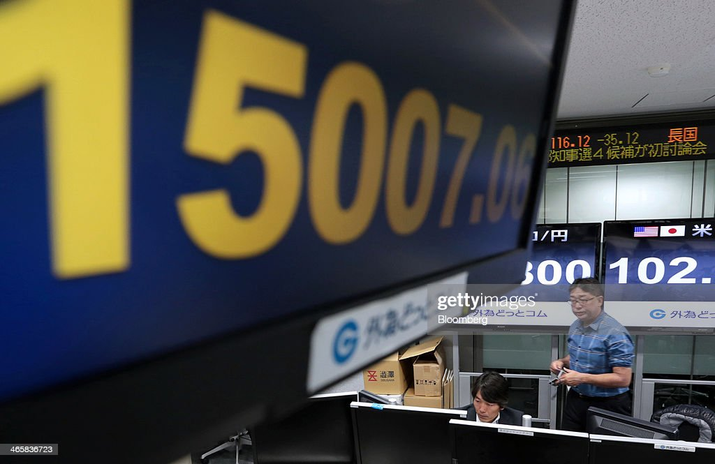 An electronic monitor flashes the closing price of the Nikkei 225 Stock Average at a foreign exchange brokerage in Tokyo, Japan, on Thursday, Jan. 30, 2014. Japanese stocks fell, with the Topix index closing at its lowest in six weeks, after the yen gained as the Federal Reserve pushed ahead with stimulus cuts amid turmoil in emerging markets. Photographer: Yuriko Nakao/Bloomberg via Getty Images
