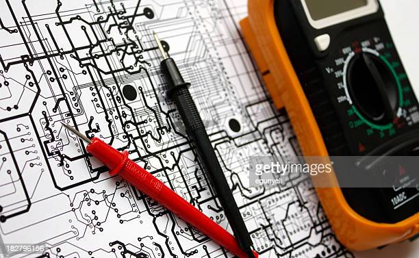 An electronic schematic and multimeter on a blueprint