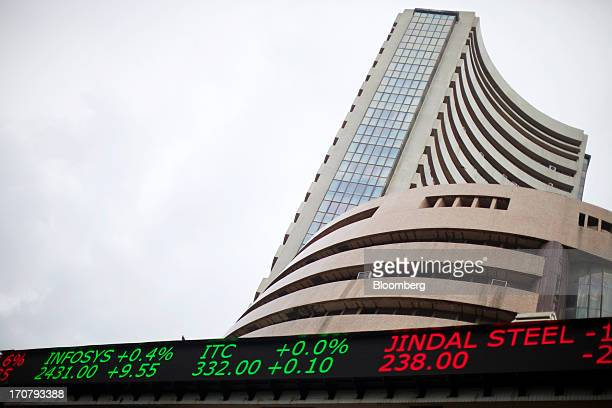 An electronic ticker board indicates stock prices for Infosys Ltd from left ITC Ltd and Jindal Steel Power Ltd outside the Bombay Stock Exchange in...
