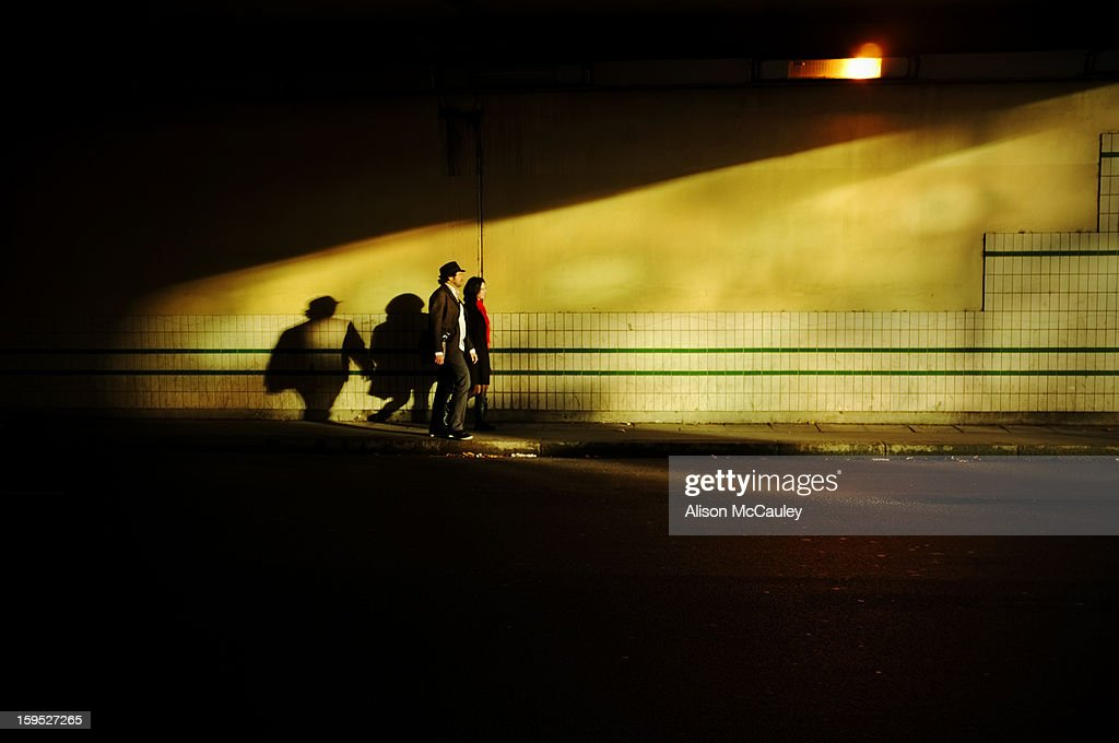 CONTENT] An elegant couple, holding hands, walk through an urban underpass. They are walking into the golden light.