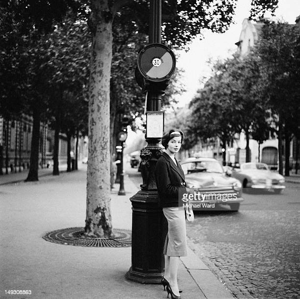 An elegant young lady standing at a bus stop in Paris 1959