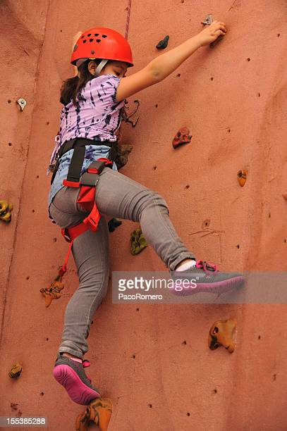 An elementary age girl climbing indoor gym wall