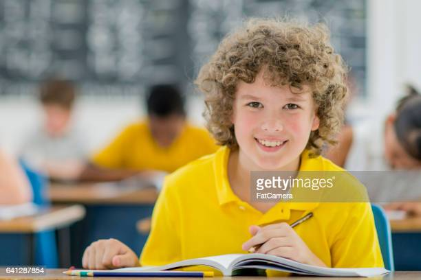 An elementary age student is working at his desk in his notebook. He is smiling and looking at the camera.