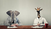An elephant and a giraffe dressed as business people .'n