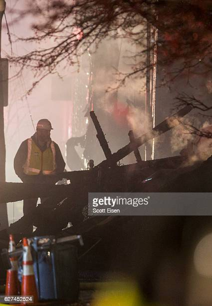 An eletrical worker looks at a fallen power pole at the scene of a 10alarm fire near Berkshire St on December 3 2016 in Cambridge Massachusetts...