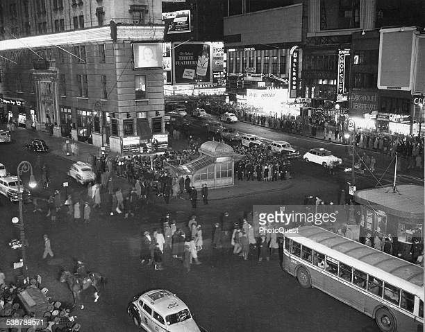 An elevated night view of people gathered in Times Square to get early election returns on the Time Building electric sign and television screen New...