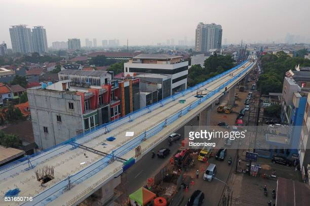 An elevated track for the Jakarta Mass Rapid Transit stands under construction as vehicles travel along a road in this aerial photograph taken in...