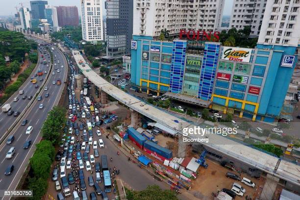 An elevated track for the Jakarta Mass Rapid Transit stands under construction as vehicles wait in congested traffic in this aerial photograph taken...