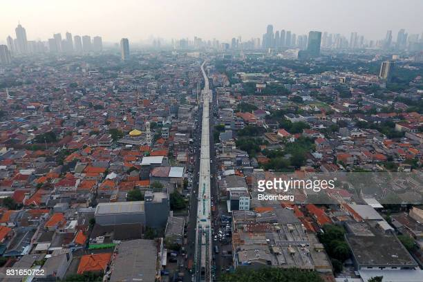 An elevated track for the Jakarta Mass Rapid Transit stands under construction among lowrise buildings as skyscrapers stand in the distance in this...
