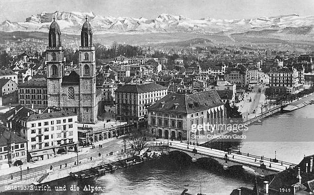 An elevated view of the city of Zurich the historic buildings of the old town and the bridge across the river and the surrounding snow covered Alps...