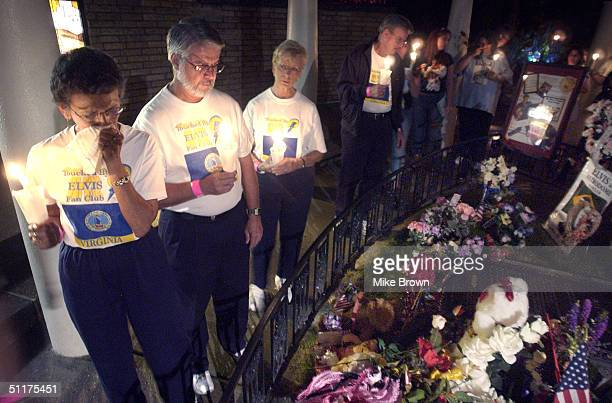 An Elvis fan weeps as she passes Elvis Presley's grave during the candle light vigil August 15 2004 at Graceland in Memphis Tennessee The vigil is...