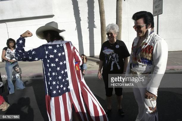 An Elvis Presley impersonator admires a woman's patriotic jacket as they prepare to participate in the 'Helldorado' Parade in Las Vegas 14 May 2005...