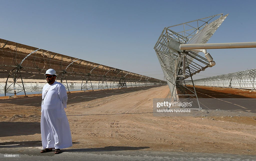 An Emarati stands in front of rows of parabolic shaped mirrors at the Shams 1, Concentrated Solar power (CSP) plant, in al-Gharibiyah district on the outskirts of Abu Dhabi, on March 17, 2013 during the inauguration of the facility. Oil-rich Abu Dhabi on Sunday officially opened the world's largest Concentrated Solar Power (CSP) plant, which cost $600 million to build and will provide electricity to 20,000 homes.