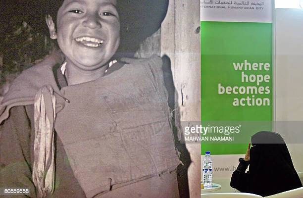 An Emarati woman is seen sitting beind a huge poster of a South American boy at at the Dubai International Humanitarian Aid and Development...