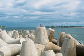 An embankment of Baltic sea at the city Baltiysk on cloudy summer day, a view to the gray seascape, waves and big stone blocks at pier, the most western point of Russia, Kaliningrad region.