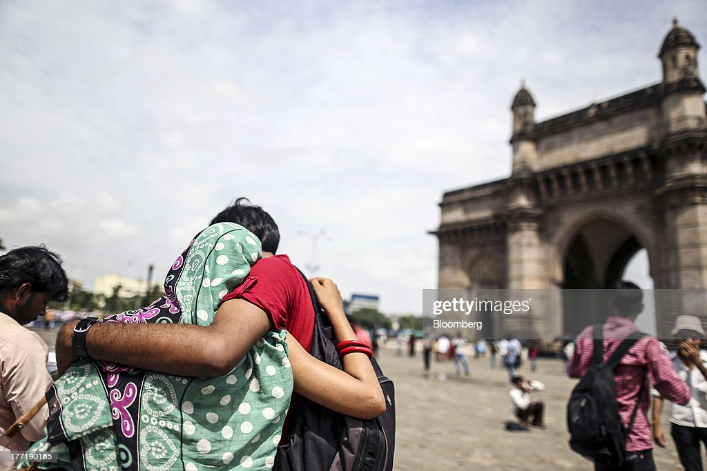An embracing couple stand near the Gateway of India memorial building in Mumbai, India, on Wednesday, Aug. 21, 2013. The prospect of an indecisive 2014 election in India is eroding confidence among global investors that the government can stop the rupees worst drop in more than two decades. Photographer: Dhiraj Singh/Bloomberg via Getty Images