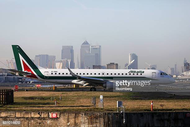 An Embraer E190 passenger aircraft operated by Alitalia SpA prepares to take off from London City Airport against a backdrop of the Canary Wharf...