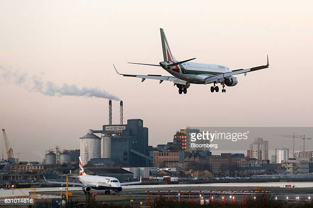 An Embraer SA passenger aircraft operated by Alitalia SpA lands at London City Airport against a backdrop of the Tate Lyle Plc sugar refinery in...