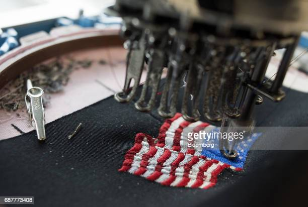 An embroidery machine stitches an American flag design onto a baseball hat at the Graffiti Caps production facility in Cleveland Ohio US on Tuesday...