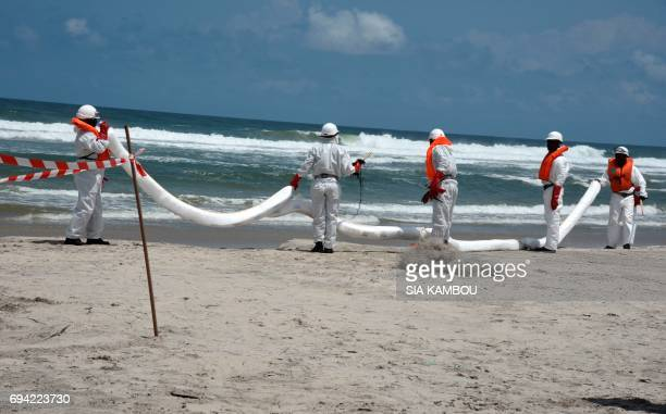 An Emergency Intervention Team specialised in marine pollution place an absorbent boom to prevent water pollution on a beach of Assinie on June 9...